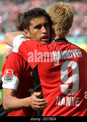 Hanover's Mike Hanke and Karim Haggui cheer after the goal to the score 1-0 during German Bundesliga match Hanover - Stock Photo
