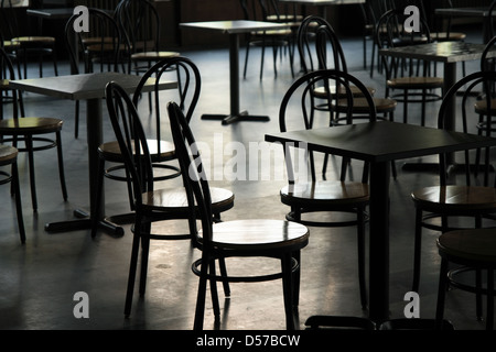 Tables and chairs in a cafeteria. Light coming from the window. - Stock Photo