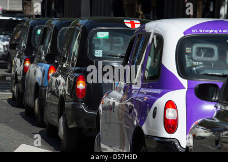 Row of black taxi cabs in the city of London, England. - Stock Photo