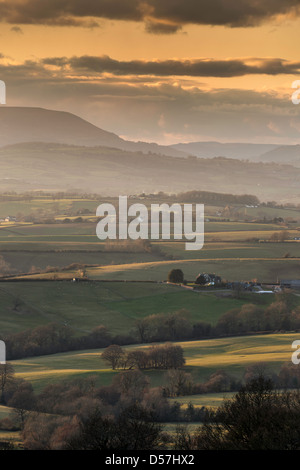 VIEW OVER THE VALE OF USK TOWARDS ABERGAVENNY AND COITY MOUNTAIN AT SUNSET WITH MIST IN VALLEYS - Stock Photo