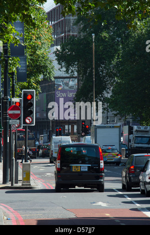 Taxi and other traffic waiting at a red traffic light in the City of London, England. - Stock Photo