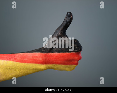 Hand painted with the flag of Germany, expressing positivity and isolated on gray background - Stock Photo