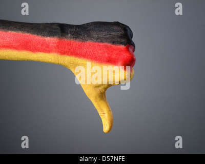 Hand painted with the flag of Germany, expressing negativity and isolated on gray background - Stock Photo