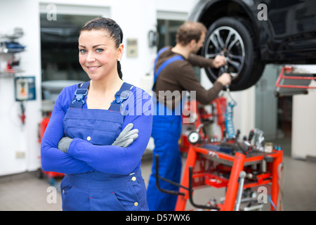 Female mechanic standing in workshop, another mechanic changes a wheel at a car on a hydraulic lift - Stock Photo