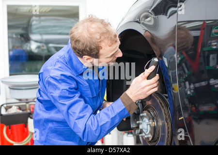 Car mechanic repairs the brakes of an automobile on a hydraulic lift - Stock Photo