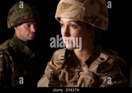 Female soldier in British Military desert uniform in foreground & male soldier in green camouflage uniform in the - Stock Photo