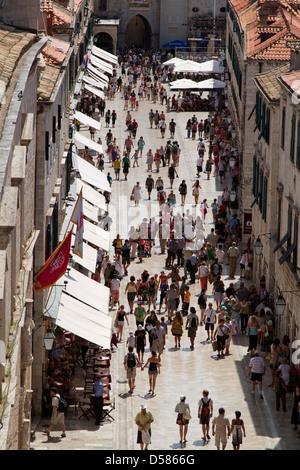 Tourists walk along the Stradun in Dubrovnik old town, Croatia - Stock Photo
