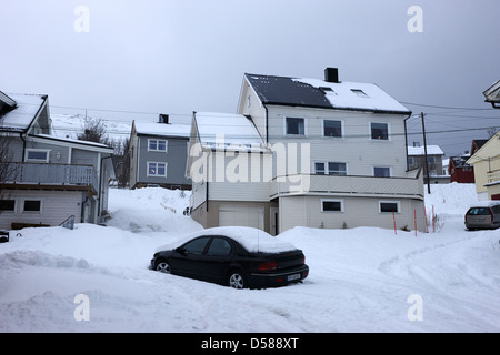 car buried in snow in front of traditional wooden home Honningsvag finnmark norway europe - Stock Photo