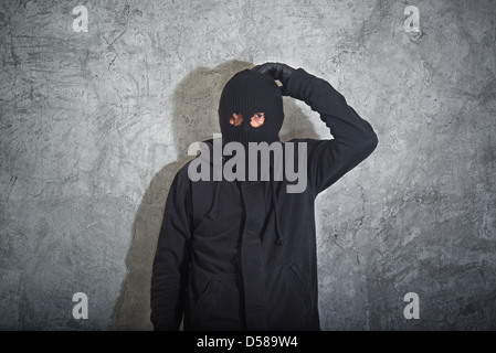 Confused burglar concept, thief with balaclava caught and arrested in front of the grunge concrete wall. - Stock Photo