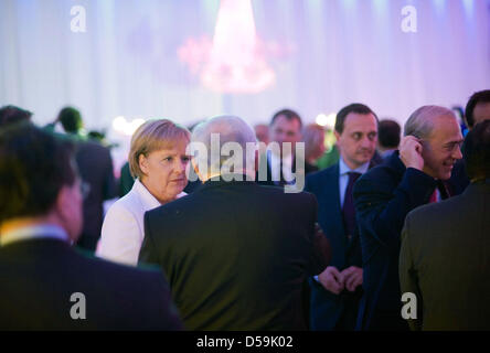 The Chancellor of Germany Angela Merkel talks to the managing director of the IMF, Dominique Strauss-Kahn (M) during - Stock Photo