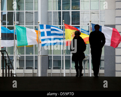 Waving flags of problem countries in front of the European Parliament building in Brussels, Belgium - Stock Photo