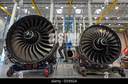 Two employees train themselves, working on a Rolls-Royce Trent 900 training jet engine (L), on the right side a - Stock Photo