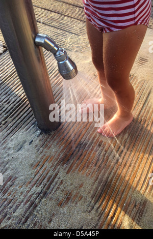Girl washing her feet from the sand - Stock Photo