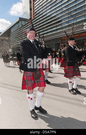 Traditional pipe band marching on Ste Catherine street in Montreal during the St Patrick's Day parade. - Stock Photo