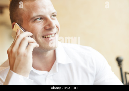 Men speaking on phone, blurred background, business building interior - Stock Photo