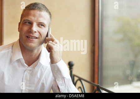 Men talking on phone, blurred background, building interior - Stock Photo