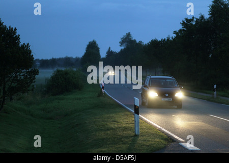 Breklum, Germany, cars in the fog on a country road - Stock Photo