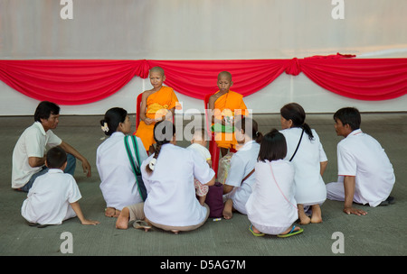 Young Buddhist monks with believers - Stock Photo