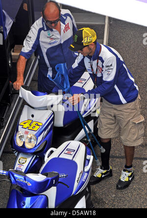 The Italian Yamaha driver and MotoGP superstar Valentino Rossi uses his crutches to descend from a scooter in the - Stock Photo