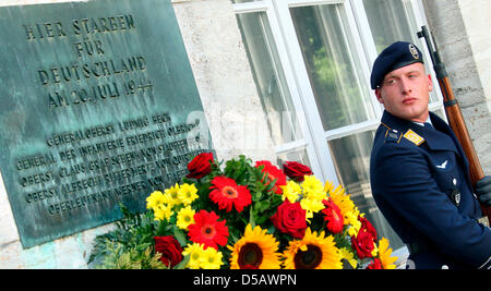 A soldier belonging to the guard of the German Federal Armed Forces stands besides a commemorative plaque for the - Stock Photo