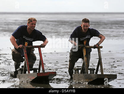 On mudflat sleighs  called 'Kreier', Bernd (L) and Thomas force their way through the mud in the course of the 27th - Stock Photo