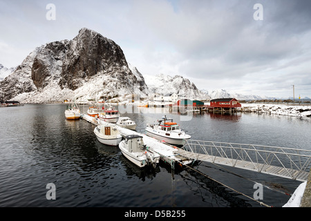 A view of boats tied up in the pretty harbour at Hamnoy, with Lilandstinden in the background - Stock Photo