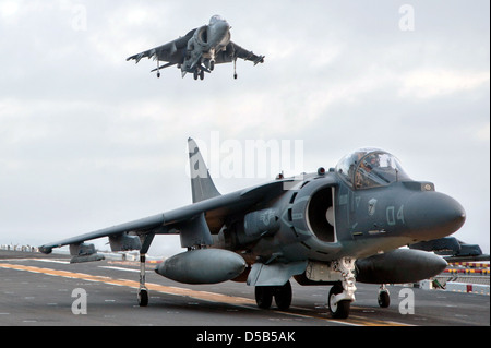 A US Marine Corps AV-8B Harrier II jet fighter aircraft lands while another waits on the flight deck of the amphibious - Stock Photo
