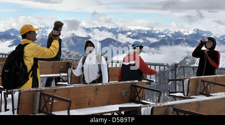 Tourists take pictures of fresh snow on the Zugspitze mountain in Garmisch-Partenkirchen, Germany, 16 August 2010. - Stock Photo