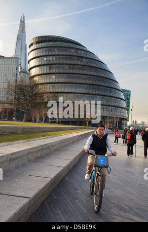 A man riding a 'Boris bike' outside City Hall on the south bank of the Thames in London. - Stock Photo