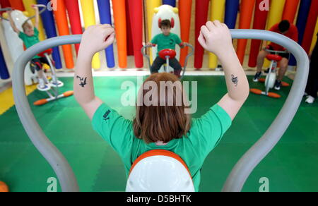 A file picture taken on 6 August 2010 shows children working out on machines at the children's gym club in the South - Stock Photo