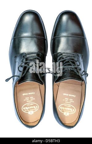 Scruffy brogues mens shoes cut out on a white background. Church's black worn formal lace up leather pair of shoes,UK. - Stock Photo