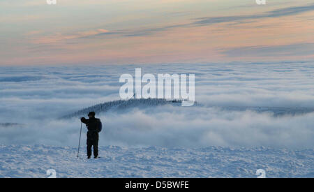 A cross country skier in front of a layer of clouds near the Brocken summit in the Harz mountain range, Germany, - Stock Photo