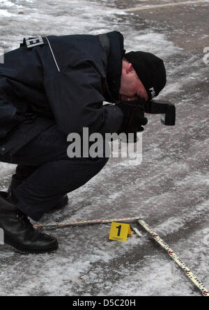 An official secures the crime scene and takes pictures of the knife in front of the Buergerhospital in Frankfurt - Stock Photo