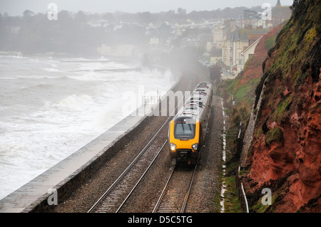 Cross Country trains Voyager train passing along the famous sea wall at Dawlish during a winter storm - Stock Photo