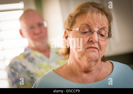 Senior Adult Couple in Dispute or Consoling in Kitchen of House. - Stock Photo