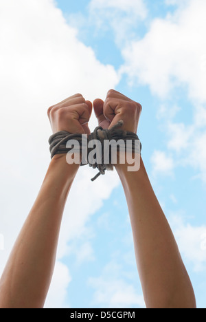 Hands tied up with rope against blue sky - Stock Photo