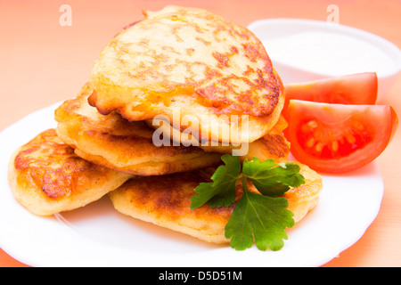 Fried potato pancakes on white plate with vegetable garnish and sour cream - Stock Photo