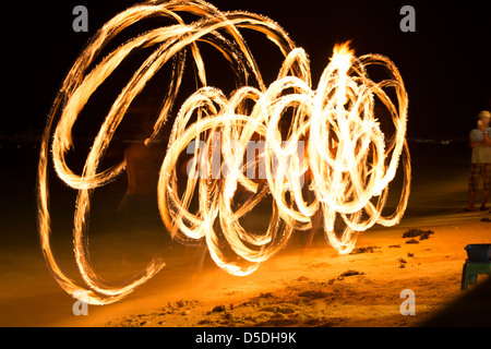 Fire artist showing off his art on Alona Beach - Stock Photo