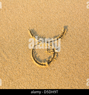Zodiac sign Taurus, drawn on the facture beach sand. (zodiac signs series) - Stock Photo
