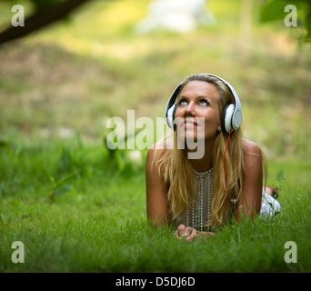 Happiness girl with headphones enjoying nature and music at sunny day - Stock Photo