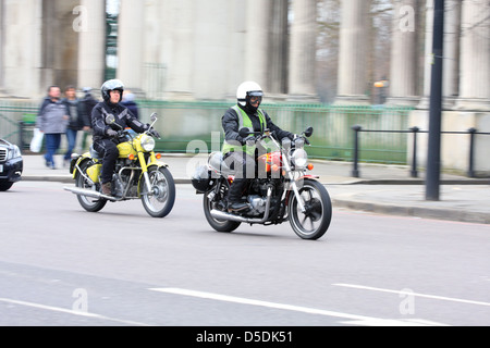 Two motorcyclists riding old motorcycles along a road in London, England. - Stock Photo