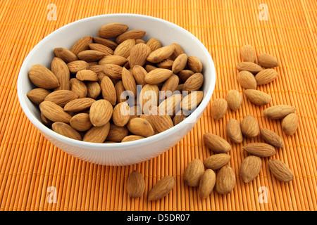 Bowl full of fresh almonds on warm orange background. - Stock Photo