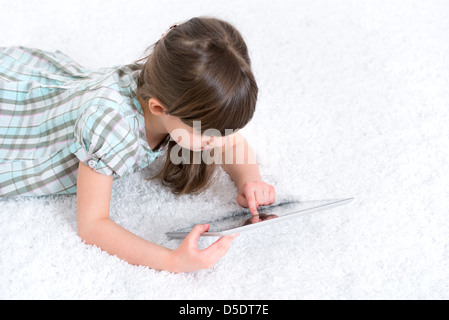 Young girl (6-7 year) looking and playing with digital tablet in a white room.