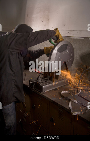 Sparks fly as a high school student uses a circular saw to cut a metal pipe in auto shop class in San Clemente, - Stock Photo