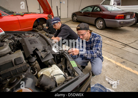 Two teenage boys work together outdoors on a car in auto shop class in San Clemente, CA. - Stock Photo