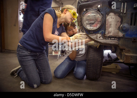 Wearing safety glasses two teenage girls work together on a car in auto shop class in San Clemente, CA. - Stock Photo
