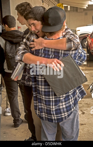 Enthusiastic male high school auto shop students hug after class in San Clemente, CA. - Stock Photo