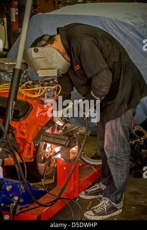 A teen boy arc welds an engine support in a high school auto shop class in San Clemente, CA, - Stock Photo