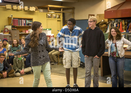 As their multiethnic classmates watch, high school drama drama students perform improvisational theatre in San Clemente, - Stock Photo