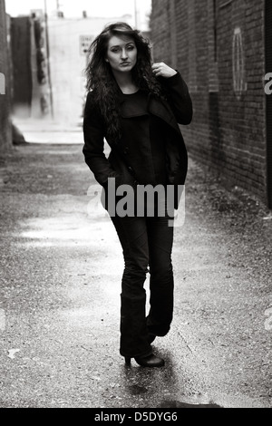 Woman in darkly dressed walking down rain soaked alley - Stock Photo